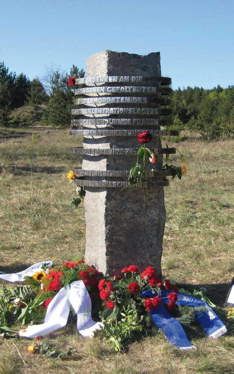 Säulenförmiger Gedenkstein mit geschmiedeter Schrift, davor Blumengestecke