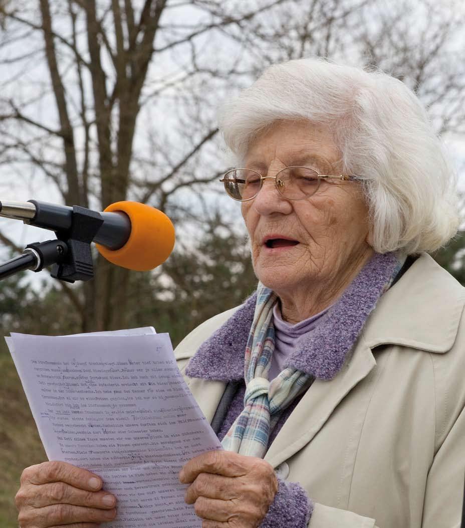 Eine alte Dame mit weißem Haar spricht in ein Mikrofon
